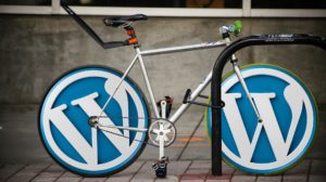 photo of a bicycle with the wordpress logo as wheels